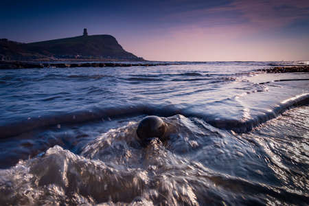 Long exposure of the incoming tide washing over rocks on the Jurassic Coast Stock Photo