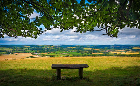 A lonely bech sits under trees on top of Wiltshore's Win Green beauty spot with a view across Cranborne Chase
