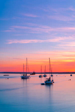 The sun goes down over the back waters of Poole Harbour near Rockley Sands Stok Fotoğraf - 119118456
