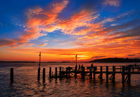 Crimson sunset over the wooden jetty at Sandbanks in Dorset with Brownsea Island visible across the water Stock Photo