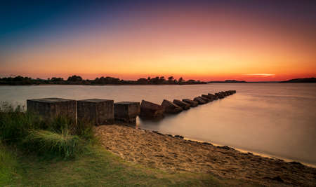 Sunset over Dragon's Teeth wartime sea defences in Poole Harbour Stok Fotoğraf - 119118481