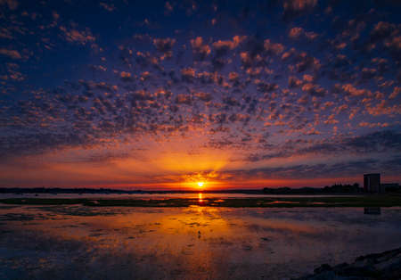 Crepuscular rays and cirrocumulus clouds create a spectacular sunset over Holes Bay, Poole Harbour, Dorset