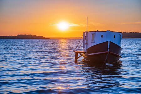 Sunlit Houseboats in Poole Harbour at sunset Stock Photo