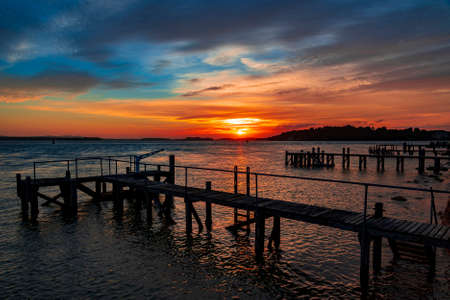Crimson sunset over the wooden jetty at Sandbanks in Dorset with Brownsea Island visible across the water Stok Fotoğraf - 119118521