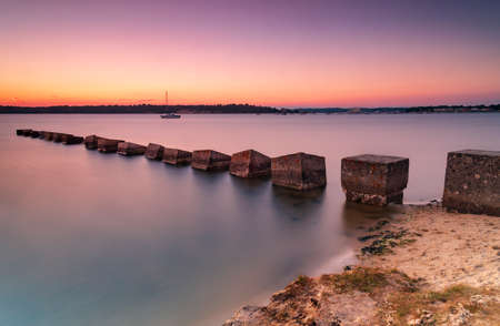 Sunset over Dragons Teeth wartime sea defences in Poole Harbour Stok Fotoğraf
