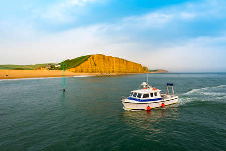 Yellow sandstone cliffs tower over a small fishing vessel at the mouth of West Bay harbour Stok Fotoğraf