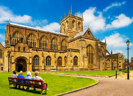 Four people sit on a bench looking at Sherborne Abbey in bright sunshine Stok Fotoğraf - 119118530