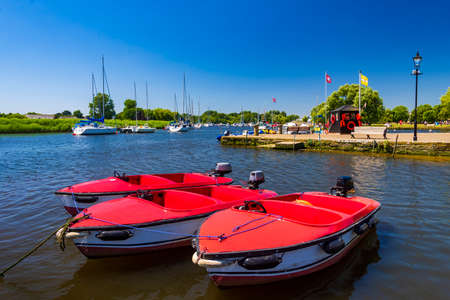 Three red leisure boats on the riverside at Christchurch Quay, Dorset Stok Fotoğraf - 119118540