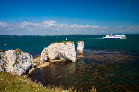White chalk cliffs of Old Harry Rocks and boats in Dorset Stok Fotoğraf