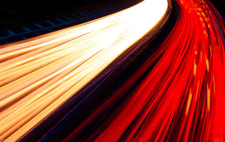 Red and white light trails streak around a bend caused by multiple car headlights and tail lights
