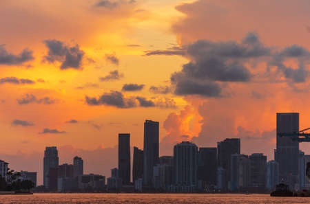 Shoreline view of Miami City Downtown district buildings at sunset