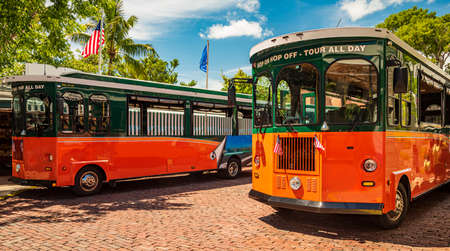 Tourists  travel on historic, orange Trolley Buses of Key West, Florida