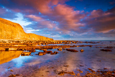 Deep blue skies are contrasted against the golden cliffs of the Jurassic Coastline at Kimmeridge Bay in Dorset Stock Photo