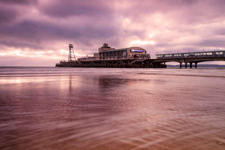 Colourful skies over Bournemouth Pier are reflected in the water