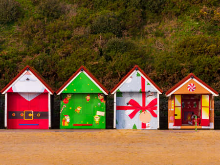 A row of colourful Christmas themed beach huts on the promenade at Bournemouth sea front