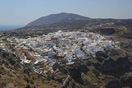 thira: The city of Fira on the edge of the volcanic caldera  Mesa Vouno with Ancient Thira in the back  Stock Photo