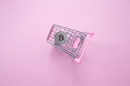 Silver bitcoin in shopping truck on a millennial pink background. Top view. Minimalism. Horizontal orientation.