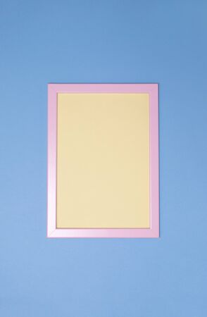 Empty pink photoframe with yellow paper inside on blue background. Copy space. Top view. Vertical Banco de Imagens - 124971874