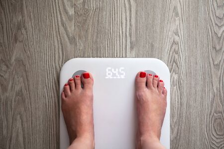 Woman stands on white modern electronic scales, which show 64.5 kg. Only feet are visible. Scales stand on gray wooden floor. Copy space. Healthy lifestyle, diet, weight loss concept. Top view. 版權商用圖片