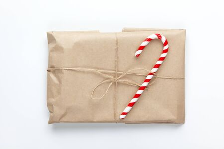 Christmas gift wrapped in craft paper, tied with scourge, decorated with cane candy on white background. Simple minimal style. Flat lay. Top view. Do it yourself, celebration concept.