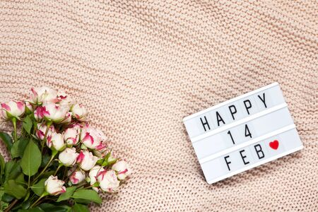 Bouquet of small roses on dusty pink blanket, lightbox with inscription Happy 14 FEB that means Valentine's Day. Flat lay. Top view. February 14th celebration concept. Horizontal, copy space.