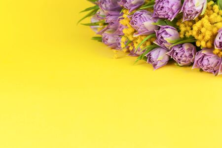 Bouquet of lilac tulips and yellow mimosas on yellow background, copy space, side view, closeup. March 8, February 14, birthday, Valentine's, Mother's, Women's day celebration, spring concept.