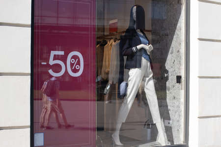 Showcase of clothing store in season of discounts, mannequin in modern comfortable womens clothing, banner with inscriptions of discount 50 percent. Concept shopping, black friday, sales. Horizontal