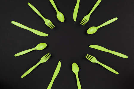 Biodegradable reusable recyclable green forks, spoons, knifes made from corn starch or oats laid out like sun or flower on black background. Eco, zero waste concept. Flat lay. Horizontal. Closeup. Stock fotó
