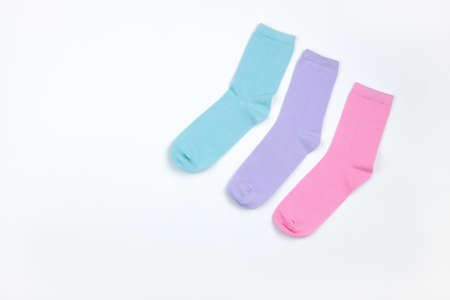 Multicolored children's socks without pattern, laid out in corner of frame, on white background with copy space, flatly, minimal style. Concept children's clothing, housekeeping.