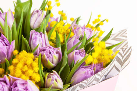 Bouquet of lilac tulips and yellow mimosas in pink box on white background, closeup, side view. March 8, February 14, birthday, Valentine's, Mother's, Women's day celebration, spring concept.