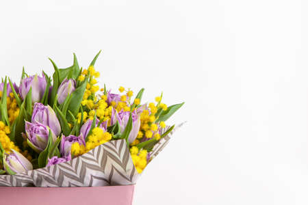 Bouquet of lilac tulips and yellow mimosas in pink box on white background, copy space, side view. March 8, February 14, birthday, Valentine's, Mother's, Women's day celebration, spring concept.