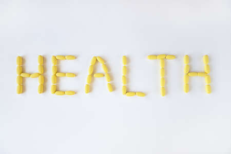 Inscription HEALTH from yellow long pills on white background, macro, close-up, copy space. Nutritional supplements concept, health, vitamins, trendy color of 2021, Illuminating. Horizontal.