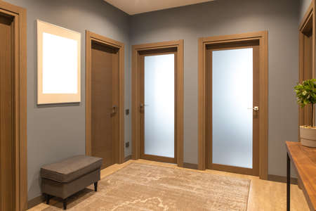 Modern entrance hallway in neutral shades of brown and gray. tones. On the wall there is a photo frame with a mockup. The concept is fashionable interior design, the use of natural materials.