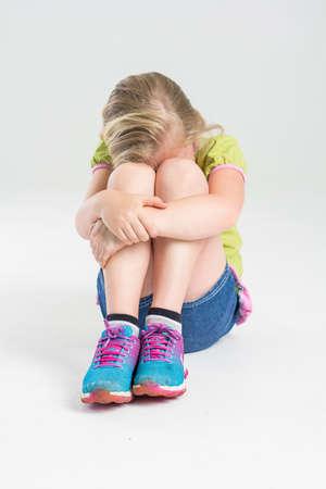 hugging knees: Blonde preschooler hugging knees, hiding face in her knees, afraid