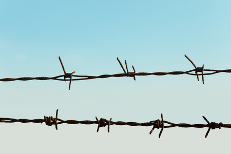Barbed wire fence of a farm, blue sky on background Stock Photo