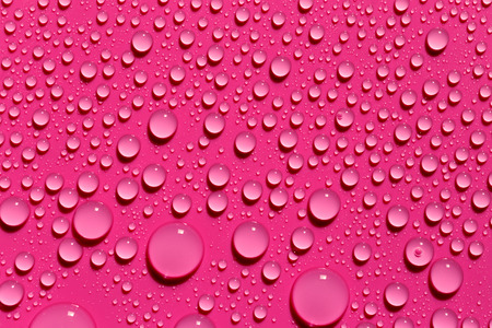 Drops of water on a fuchsia color surface, abstract background