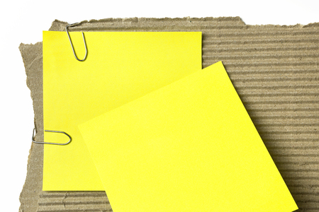 Two yellow sticky note on piece of cardboard