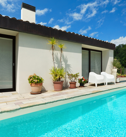 Holiday home, beautiful view of swimming pool and facade, blue sky with clouds