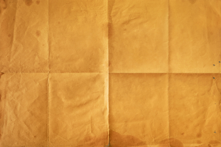 Close-up of old orange notepaper folded in eight, texture background 免版税图像