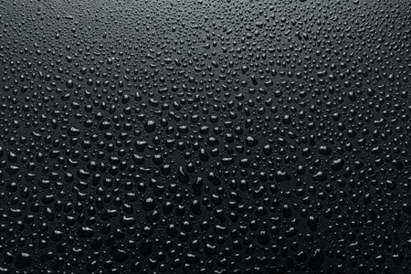 Close-up of water drops on rough surface, dark background