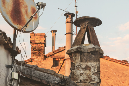 Old brick chimneys and battered antennas, view from the roofs