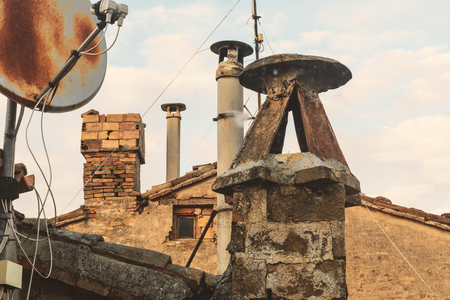 Old brick chimneys and battered antennas, view from the roofs Standard-Bild - 122876640