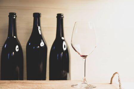 Naturaleza muerta, tres botellas negras y copa de vino tinto vacía Foto de archivo