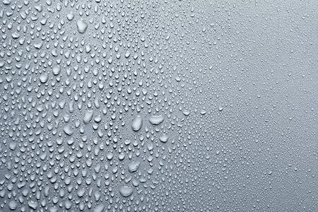 Gocce d'acqua su una superficie liscia, sfondo grigio Archivio Fotografico