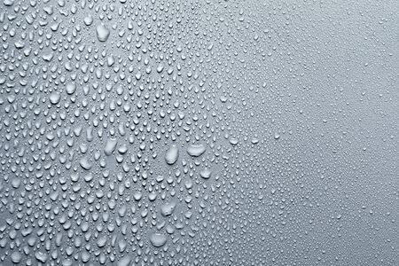 Gotas de agua sobre la superficie lisa, fondo gris Foto de archivo