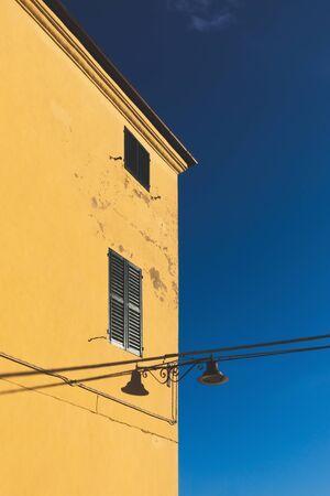 Yellow facade of old building, blue sky  Reklamní fotografie
