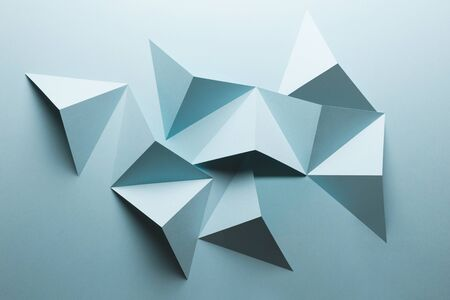 Abstract pattern made of colored paper, triangular shapes, light blue background Zdjęcie Seryjne
