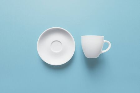Coffee break, white cup and saucer isolated on light blue Zdjęcie Seryjne