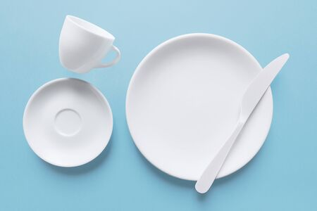 White coffee cup and dish with knife, isolated on light blue