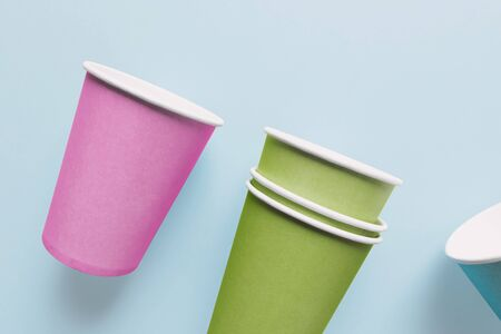 Close-up of colorful paper cups, isolated on light blue background
